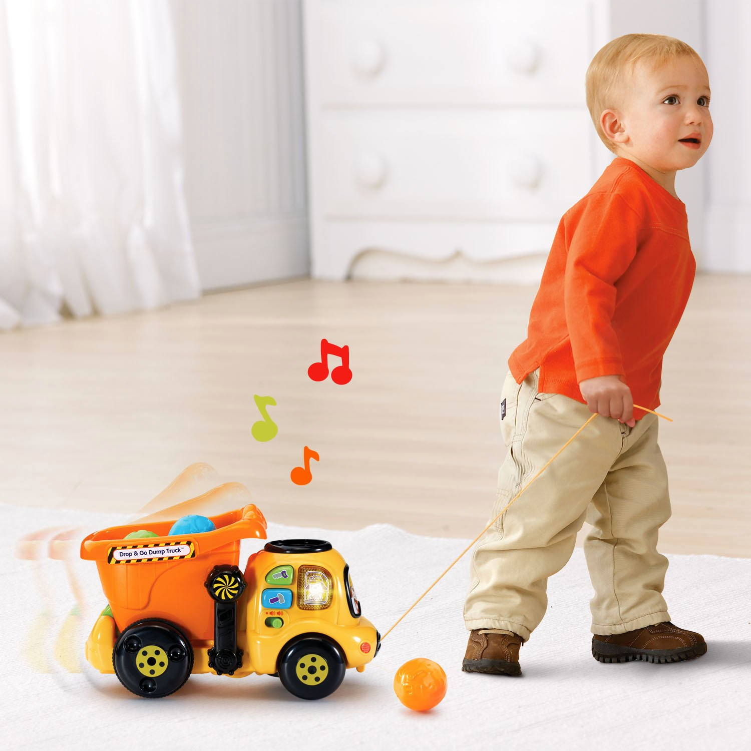 This is an image of a toddler with a VTech Drop and Go Dump Truck
