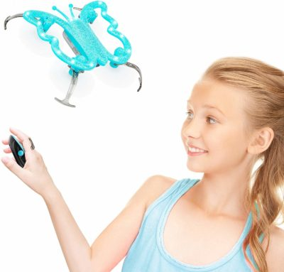 This is an image of girl playing with a toy butterfly drone