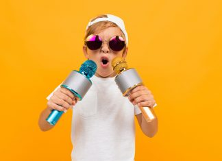 Cheeky blond boy in glasses with two microphones on a yellow background.