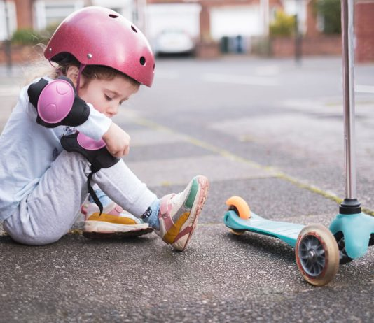 A little girl is putting on kneepads before going on her scooter