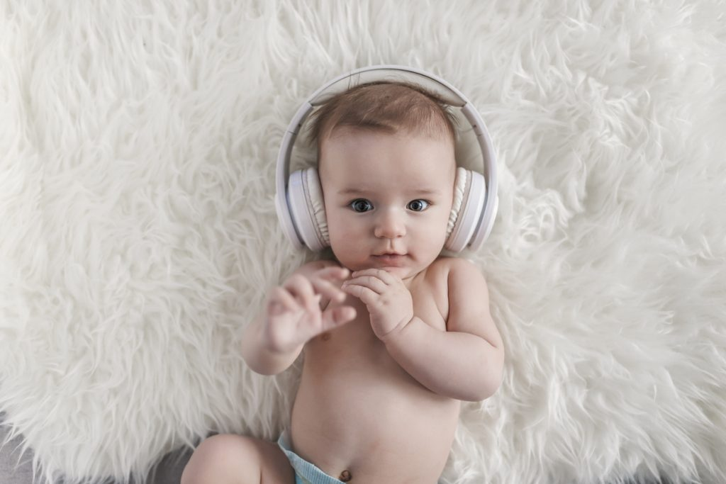 Charming baby on a white furry background with headphones listening to music while looking at the camera. Newborn baby sleeping in a fluffy blanket during the day. Little baby boy is wearing music white headphones for a party or entertainment concept.